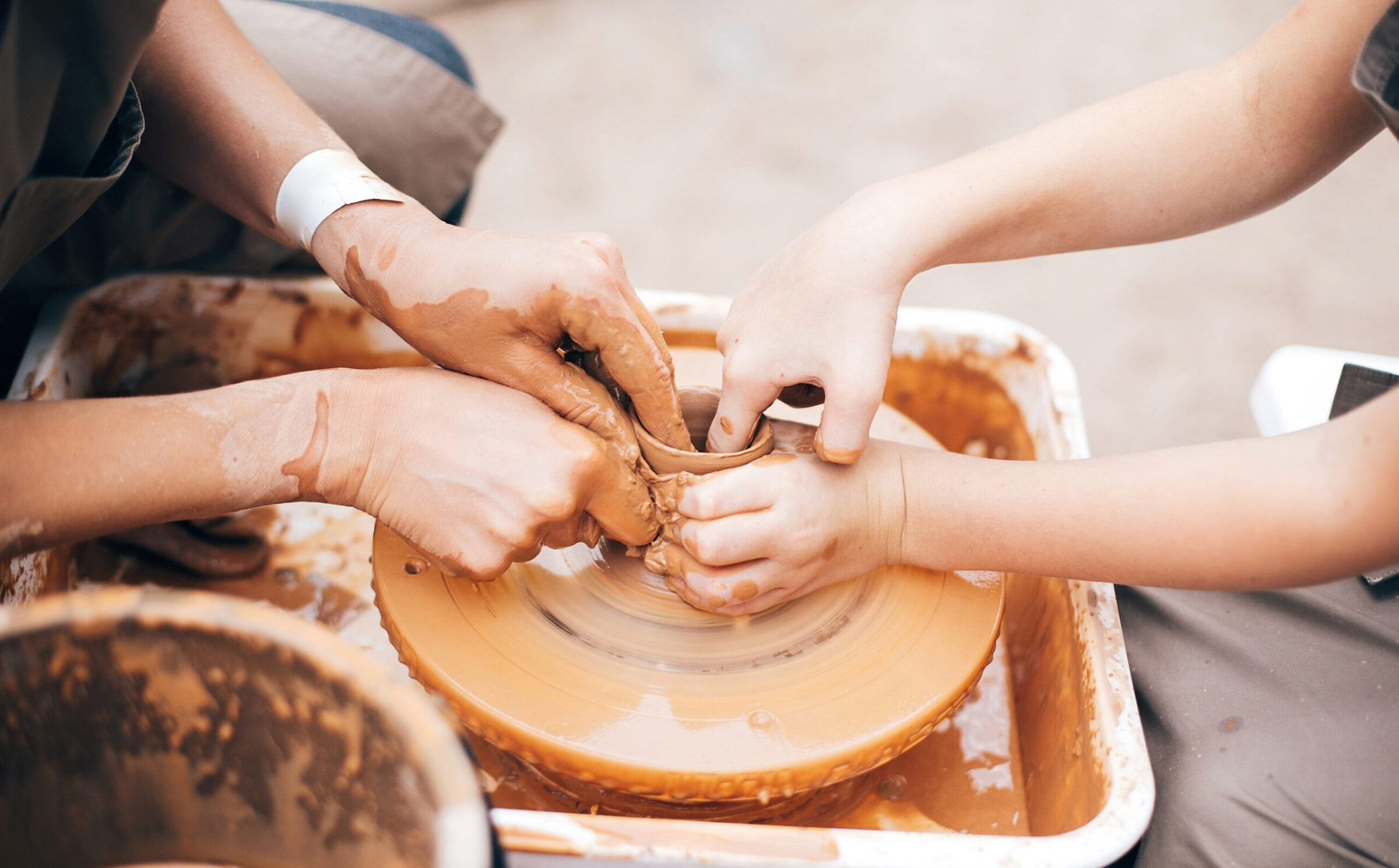 Hands of adult and child making pottery, working with wet clay closeup. Process of making bowl from clay on wheel with dirty hands. Handmade festival in summer park. Pottery workshop.
